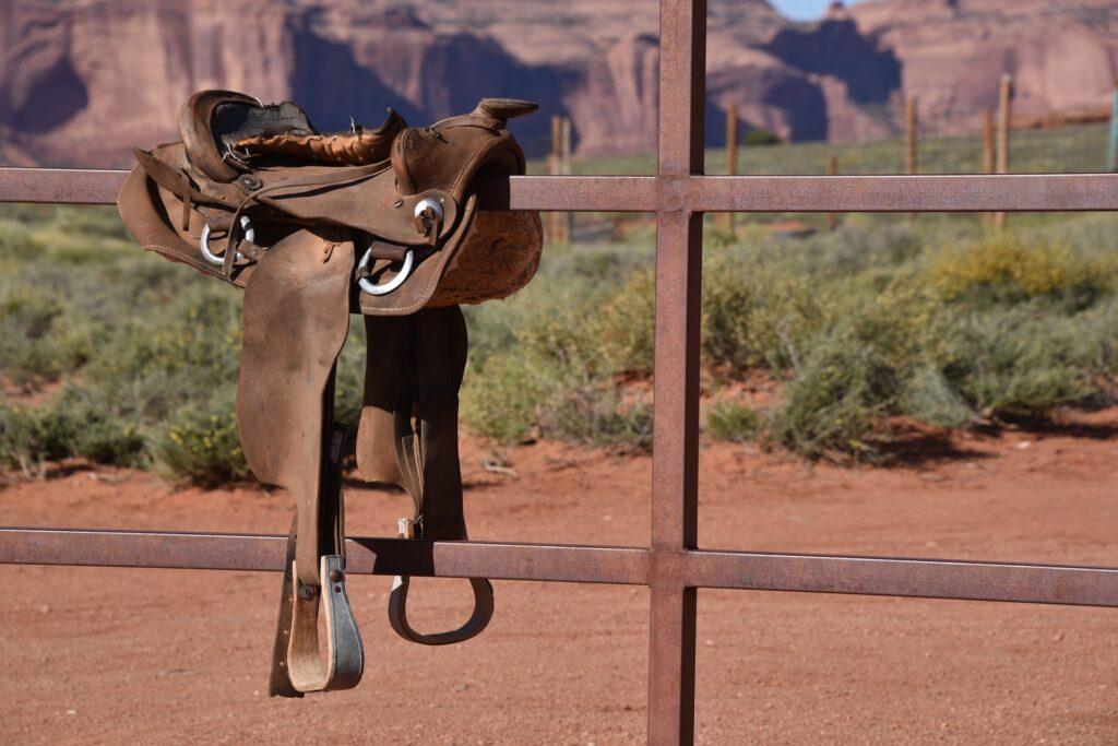 westernové sedlo hnědé barvy, pověšené na plotě